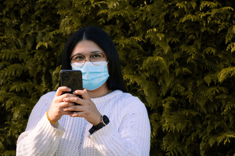 Woman with a surgical mask using the mobile in social networks. woman in the park.