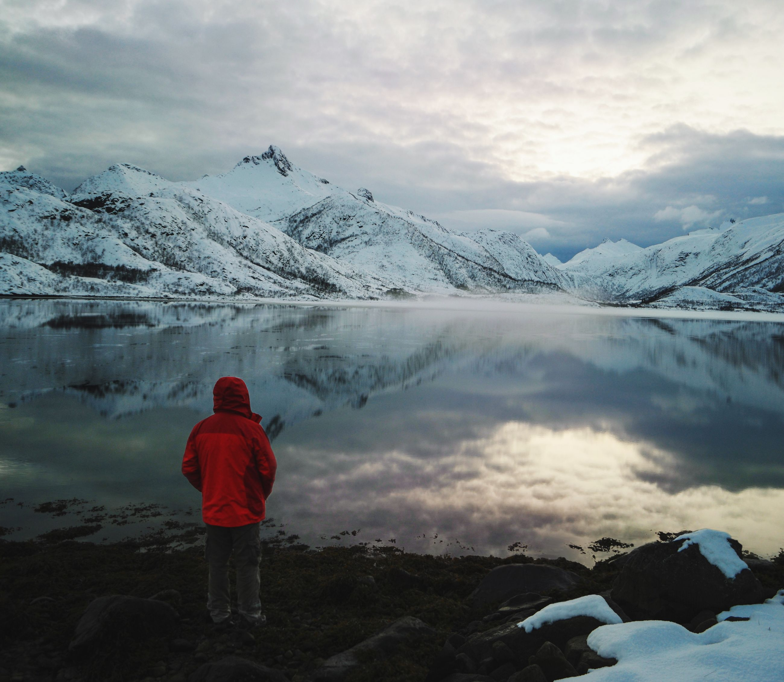 Rear View Of Man Standing In Front Of Lake With Snowcapped Mountains Reflection