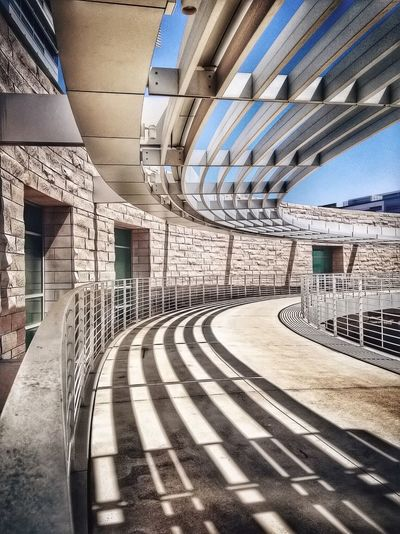 Railings and shadows against stone wall