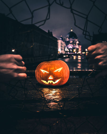 Cropped hands breaking fence against illuminated jack o lantern in city at night