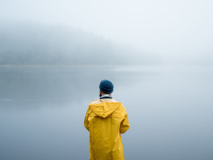 Rear view of man standing by foggy lake