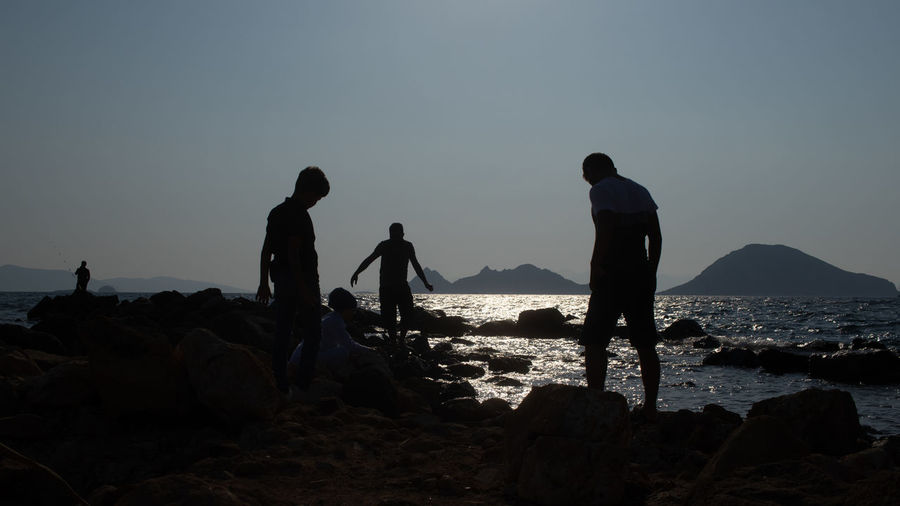 Silhouette people on rocks by sea against clear sky