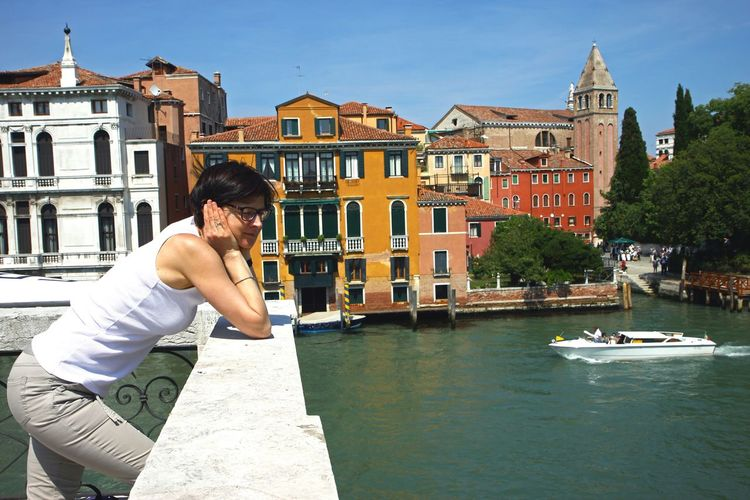 Side view of young woman standing by retaining wall at grand canal