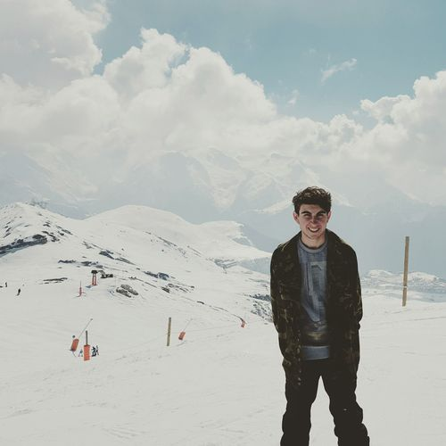 Portrait of smiling young man standing on snowcapped mountain