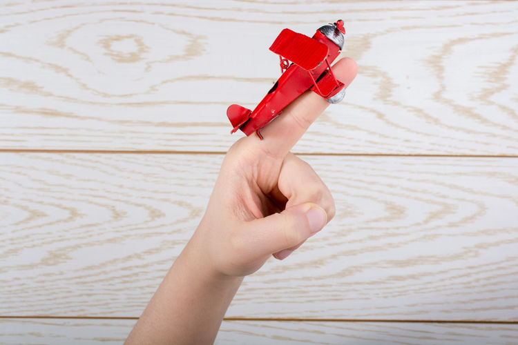 Cropped hand of person holding red model airplane