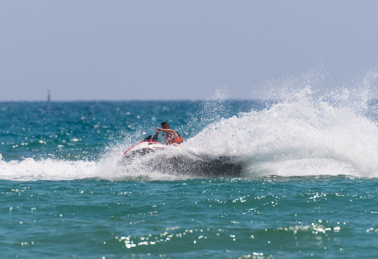 Man on jet boat on sea against clear sky during sunny day