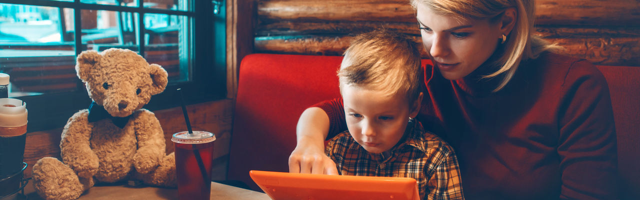 Caucasian mother and boy son choosing food meal from digital tablet touch pad menu at restaurant