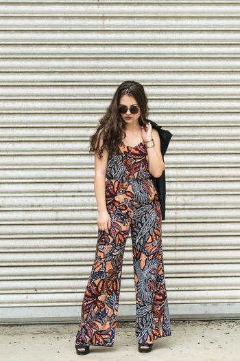 Confident Female Model Wearing Sunglasses While Standing By Closed Shutter