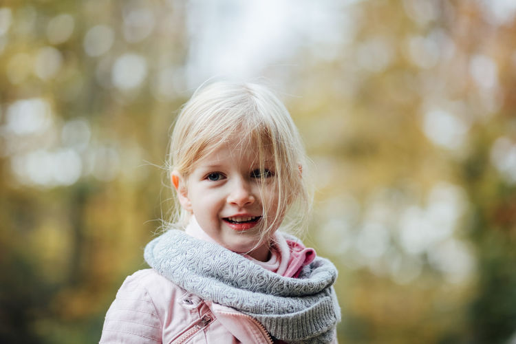 Childhood Portrait Child Happiness Blond Hair One Person Smiling Emotion Headshot Offspring Focus On Foreground Looking At Camera Hair Innocence Cute Day Cheerful Enjoyment Scarf Outdoors Warm Clothing Hairstyle