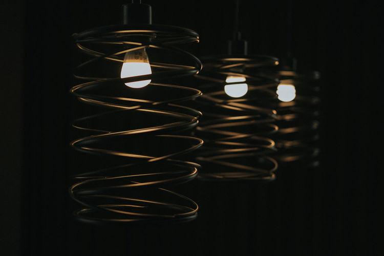 Close-up of illuminated lights hanging in darkroom