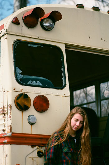 Young woman standing by an abandoned school bus