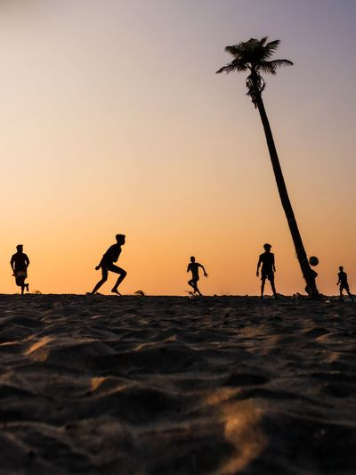 Silhouette male friends playing soccer at beach against clear sky during sunset