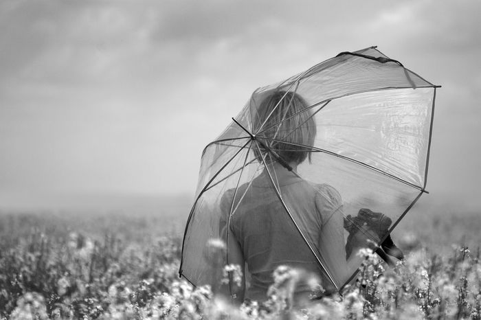 Beauty In Nature Blackandwhite Canola Field Flowers Holding Inside Landscape Melancholic Landscapes Nature Poem Rural Scene Selective Focus Self Sky Tranquil Scene Transparent Umbrella Woman Young