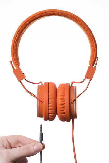Orange Headphones on white Background Close-up Day Headphones Human Body Part Human Hand Product Product Photography Sound Studio Shot Technology White Background