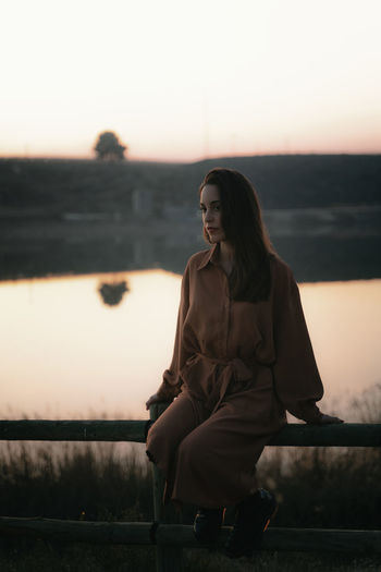 Young woman looking away while sitting against sky during sunset