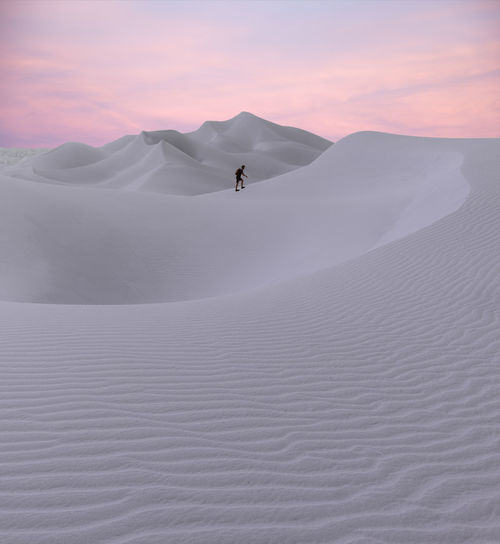 Man walking on desert against sky during sunset