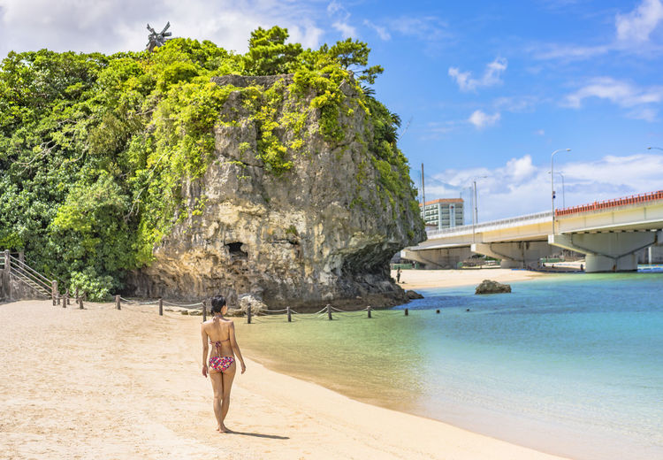 Young woman in swimsuit from behind on the sandy beach naminoue in naha city in okinawa, japan.