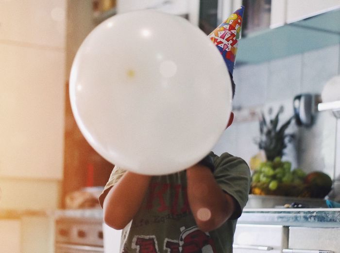 Boy with white balloon during birthday at home