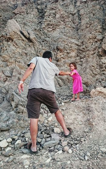 Rear View Of Father Pulling Daughter While Standing On Rocks