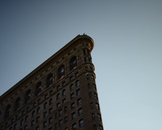 Low angle view of flatiron building against clear sky at manhattan in city