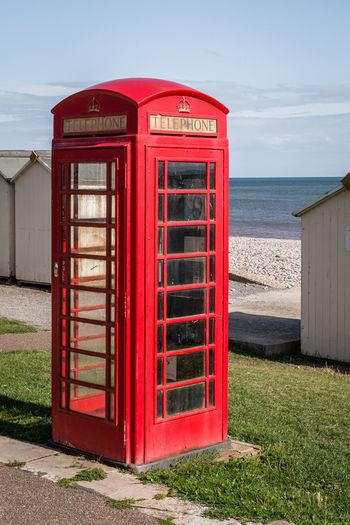 Red telephone booth by sea against sky