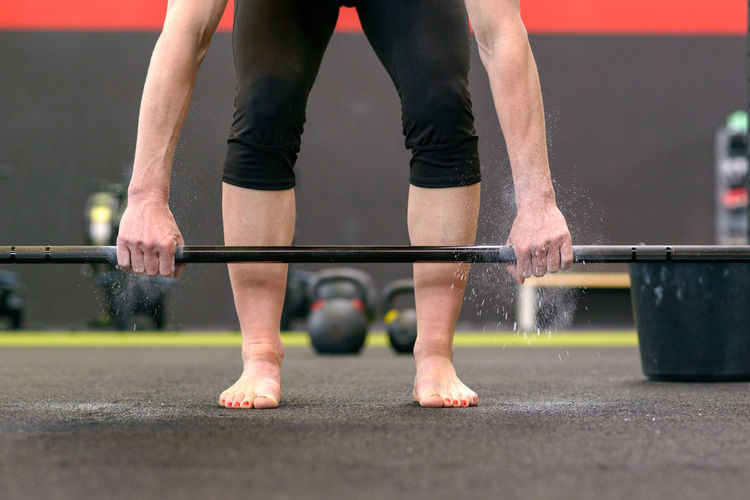 Low section of female athlete exercising with barbell in gym