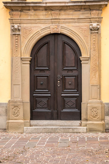 Old door of a historical building with statues and coats of arms made of stone Door Architecture Entrance Built Structure Building Exterior Closed Building The Past History Day No People Arch Safety Residential District Security Front Door Doorway Outdoors Ornate Protection