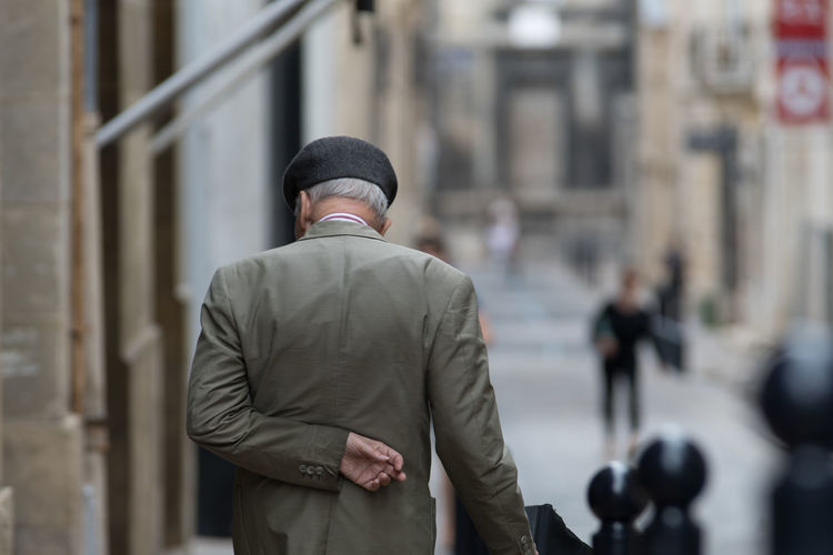 Rear view of old man standing on street