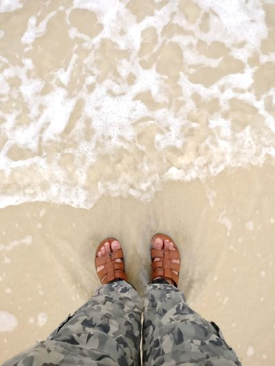 Beach time. Foam Army Style Camouflage Clothing Sandy Beach Holidays Vacation Travel Travel And Leisure Leisure Personal Perspective View From Above Beach Time Beach View Beach Day Splash Legs Feet Pants Low Section Wave Water Sea Beach Standing Men Human Leg Sand Sunlight Flip-flop Pair Slipper  Footwear Rushing Human Foot Shore