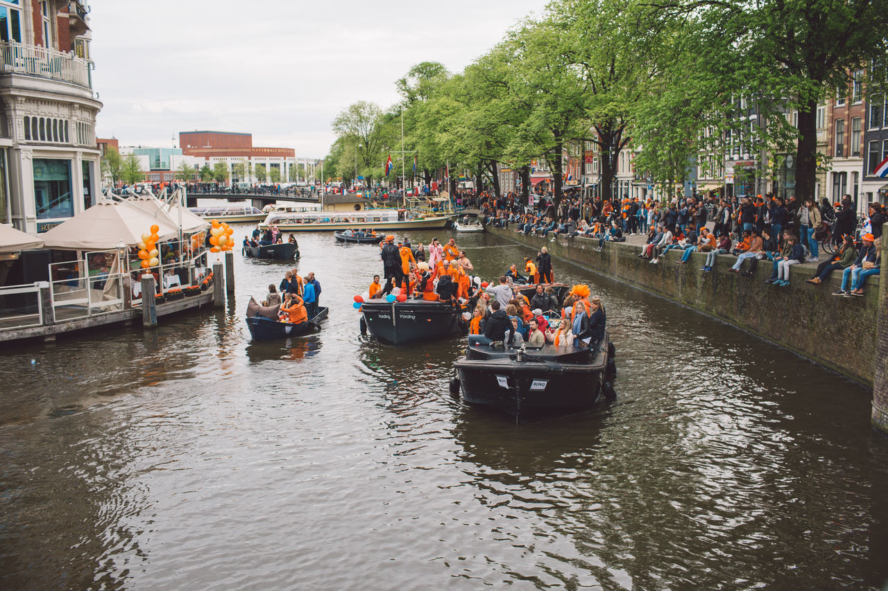 group of people, large group of people, crowd, nautical vessel, mode of transportation, water, real people, transportation, architecture, men, built structure, women, building exterior, waterfront, river, nature, day, lifestyles, outdoors, passenger craft