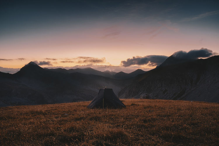 Tent on land with mountains in background against sky during sunrise