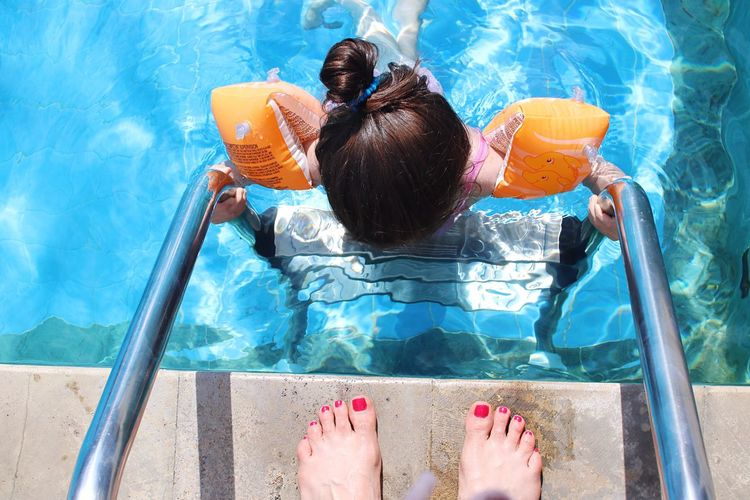 Low Section Of Woman Standing By Girl On Railing In Swimming Pool