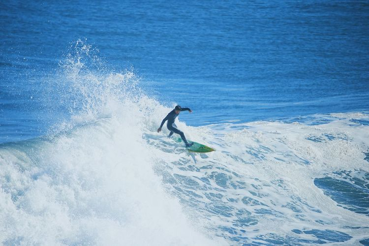 Man surfing on waves in sea