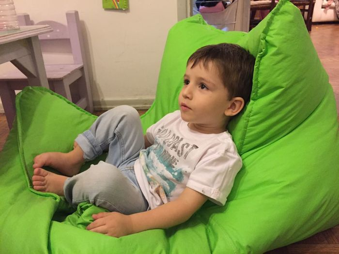 Boy Sitting On Green Bean Bag At Home