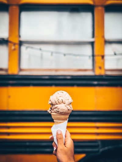Human hand holding ice cream against bus