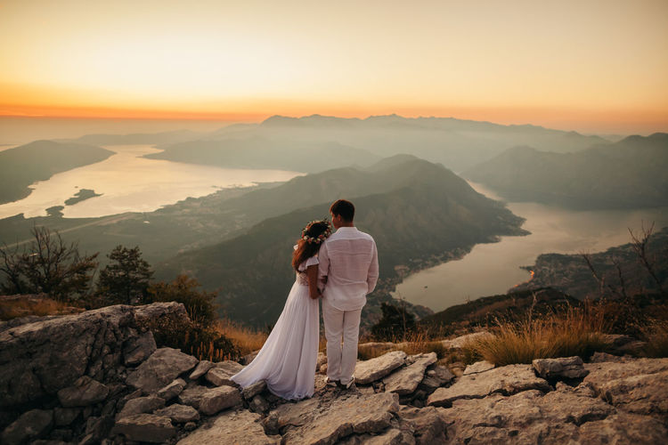 Rear view of couple standing on landscape against sky during sunset