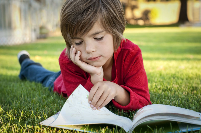 Child Childhood Grass One Person Book Learning Education Reading A Book Lying Down In Grass. Outside Kid Boy Cute♡ Young Looking Red Color