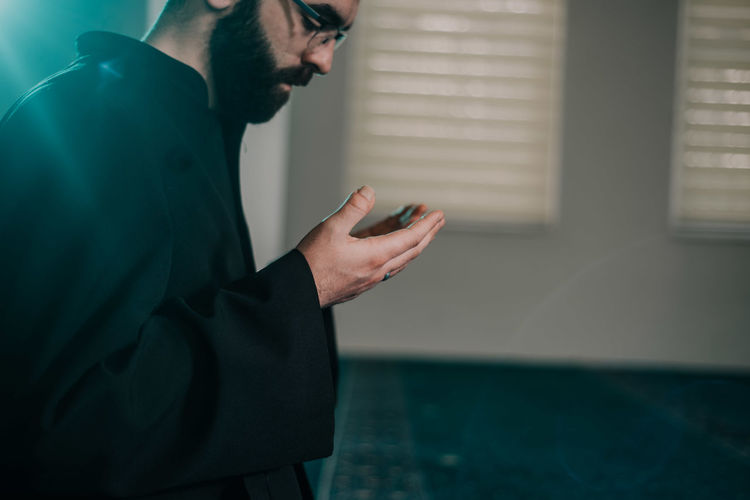 Side view of young man praying in mosque