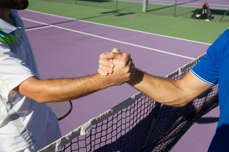 Friends shaking hands while standing on tennis court