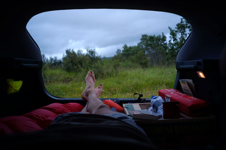 Low section of man sleeping in car at campsite against cloudy sky