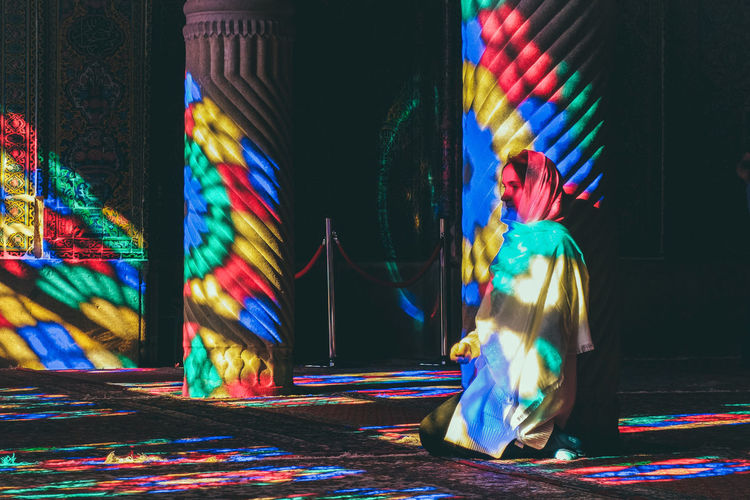 A tourist woman in the interior of Nasir Al-Molk Mosque with colorful shining stained glass windows. Nasir Persian Pink Shiny Architecture Chador Colorful Iran Molk Mosque Multi Colored Muslim Nasir-ol-molk Religion