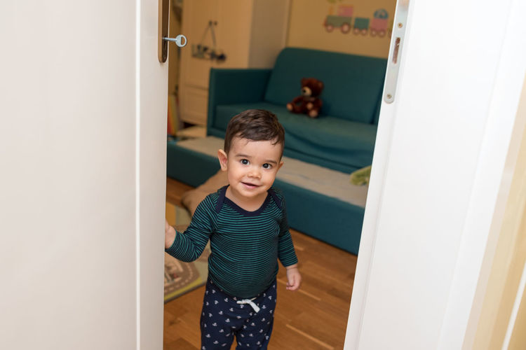 High Angle Portrait Of Boy Standing By Door At Home