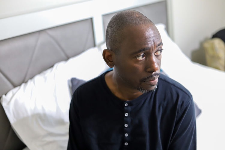 A portrait of an african-american man sitting alone on a bed and looking sad and lonely