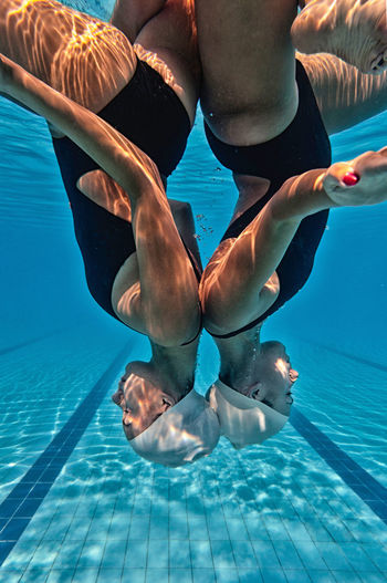 Synchronized swimming duet, underwater Aquatics Ripples Water Sport Blue Background Female Girls Rippled Swimming Swimming Pool Synchronized Synchronized Swimming Two Persons Underwater underwater photography Upside Down Water Water Sports Young Women