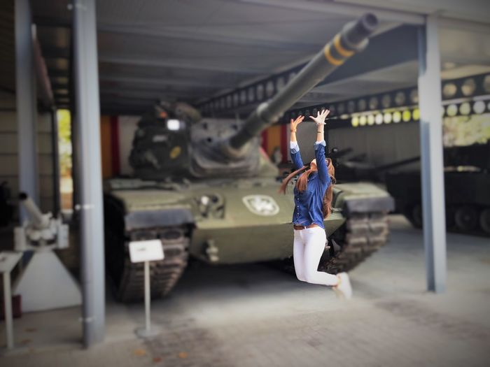 Tilt-Shift Image Of Excited Woman Jumping Against Military Tank