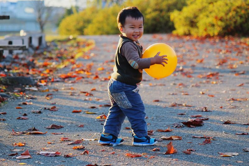 Boy Playing With Ball On Road