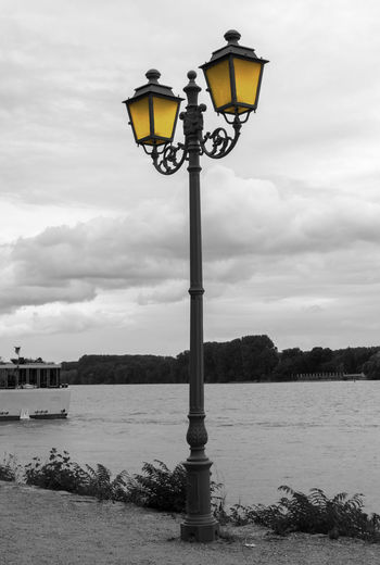 Lone street lamp on the bank of the Rhein river, Germany. Rhein Beauty In Nature Cloud - Sky Clouds And Sky Day Gas Light Illuminated Lighting Equipment Nature No People Outdoors River Sea Sky Street Lamp Street Light Water