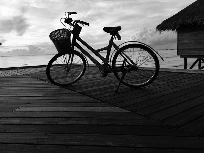 Bicycle By Water Against Sky