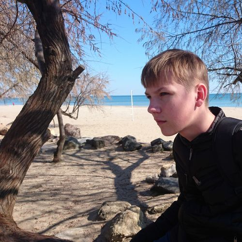 Boy looking away on land against sky