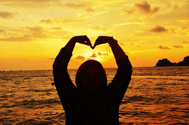 Silhouette Man Forming Heart Shape While Standing Against Sea During Sunset
